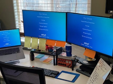 Gil's work station with sticky notes and light colored themes on his computer monitors.